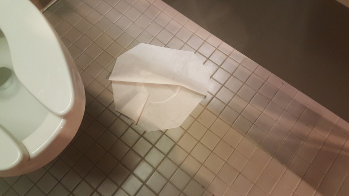 Toilet seat covers do not belong on the floor.