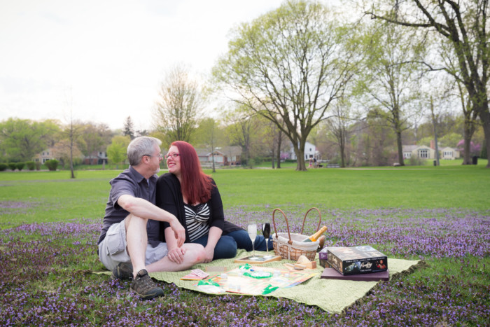 engagement photo shoot picnic with cheese, champagne, and games in a park