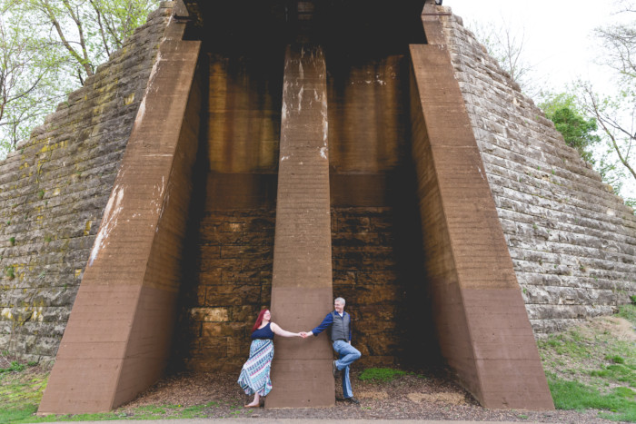 engagement photo session under a train bridge around the corner from each other
