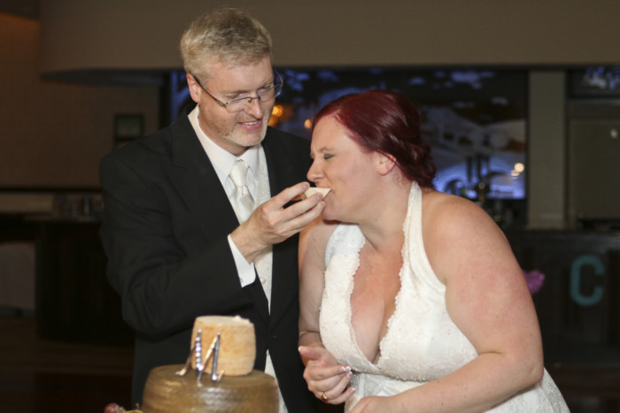 Taking a bite out of a big hunk of cheese makes for an awesome cake cutting ceremony at a wedding.