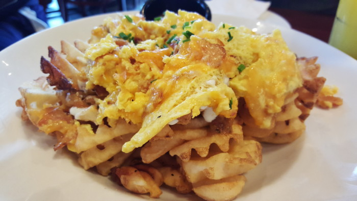 Breakfast nachos at Brunch: a plate of waffle fries, cheese, bacon, and eggs.