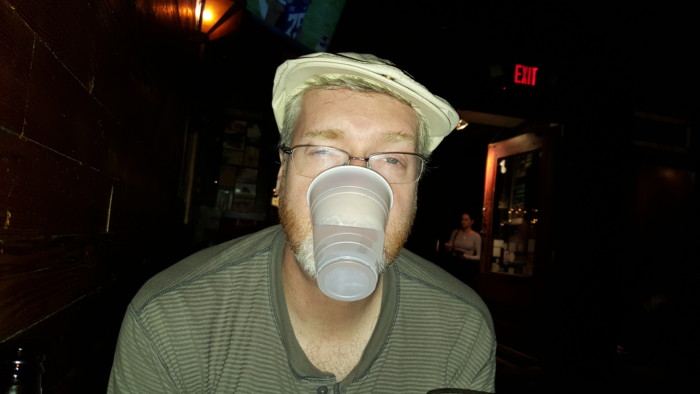 Drunk Brian holding a cup with his mouth.