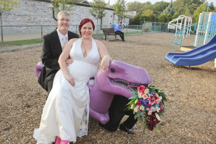 bride and groom sitting on a playground dinosaur eating the bridal bouquet