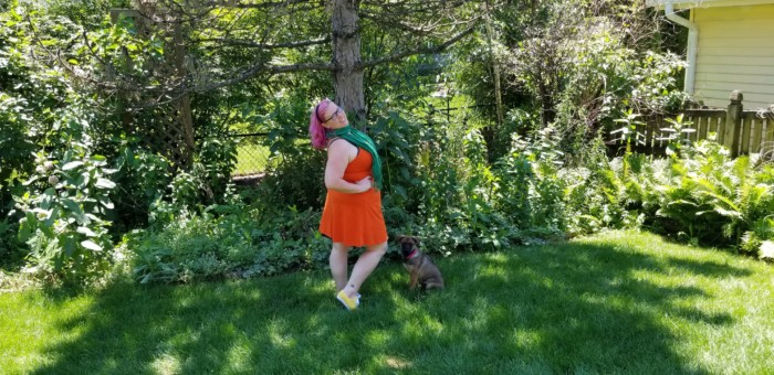 Chrissy wearing an orange dress and green scarf with yellow sneakers for an Orange Bird Disneybound.