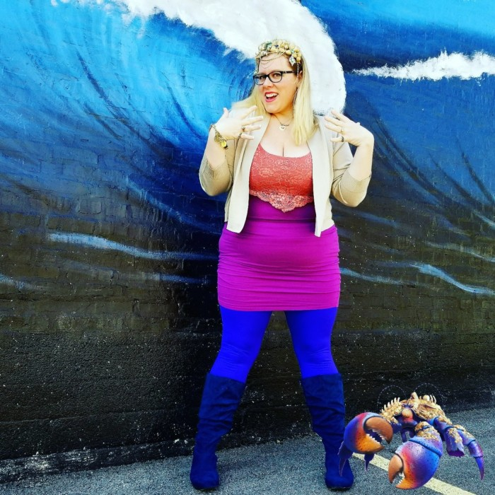 Chrissy in tamatoa Disneybound outfit in front of a mural wall