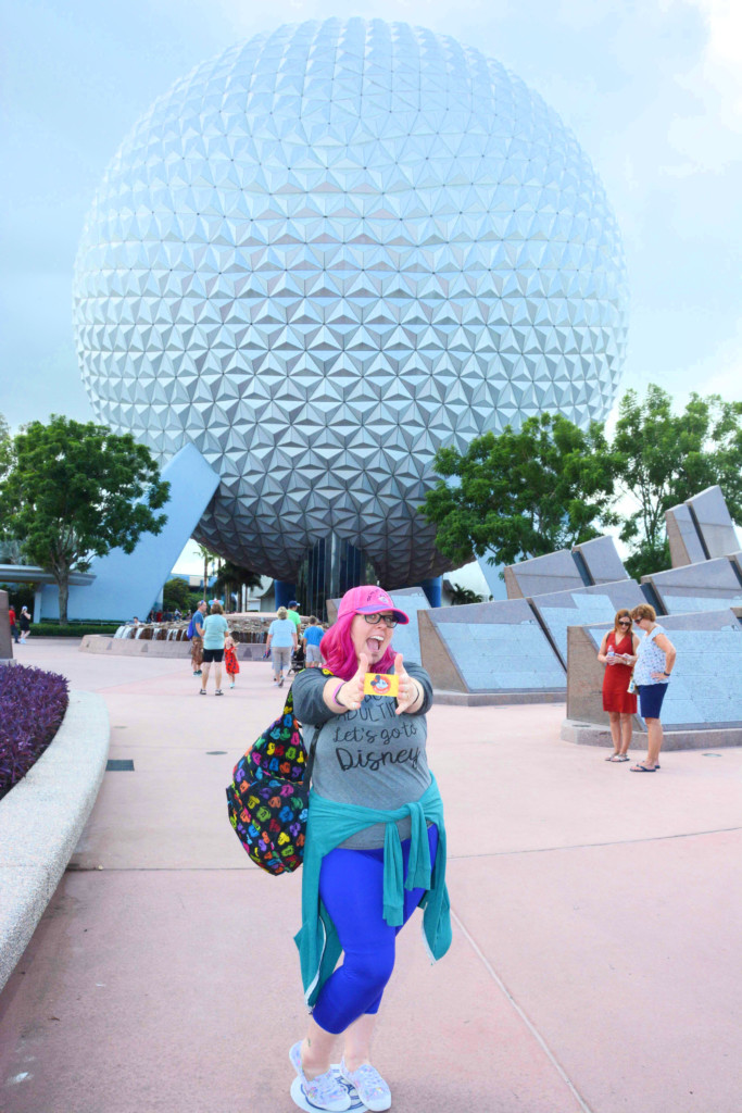 Woman Holding annual passholder card in front of EPCOT Spaceship Earth