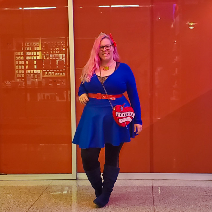 Chrissy Disneybounding as EVie from The Descendents wearing a blue dress and belt with black leggings and an evil queen purse.
