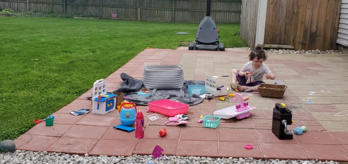 Toddler niece surrounded by toys in a backyard patio